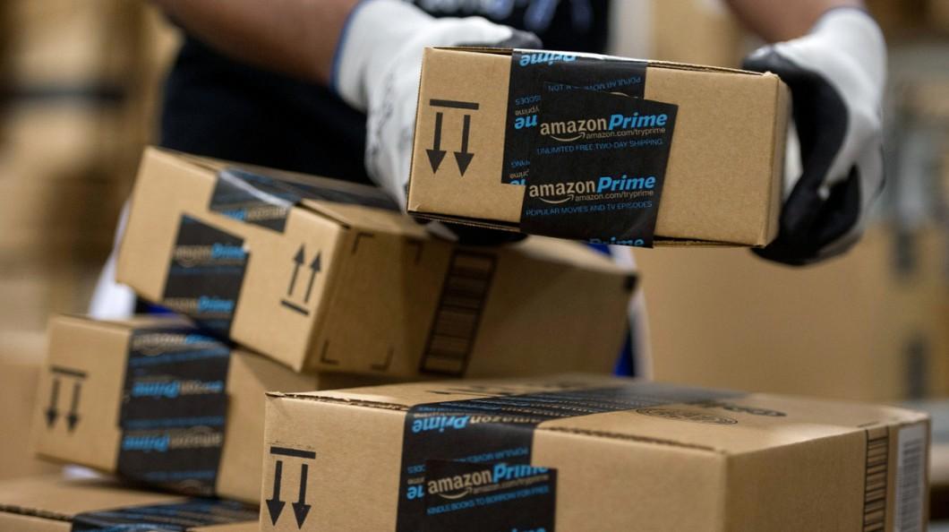 Funcionário manuseia caixas com adesivo da Amazon Prime