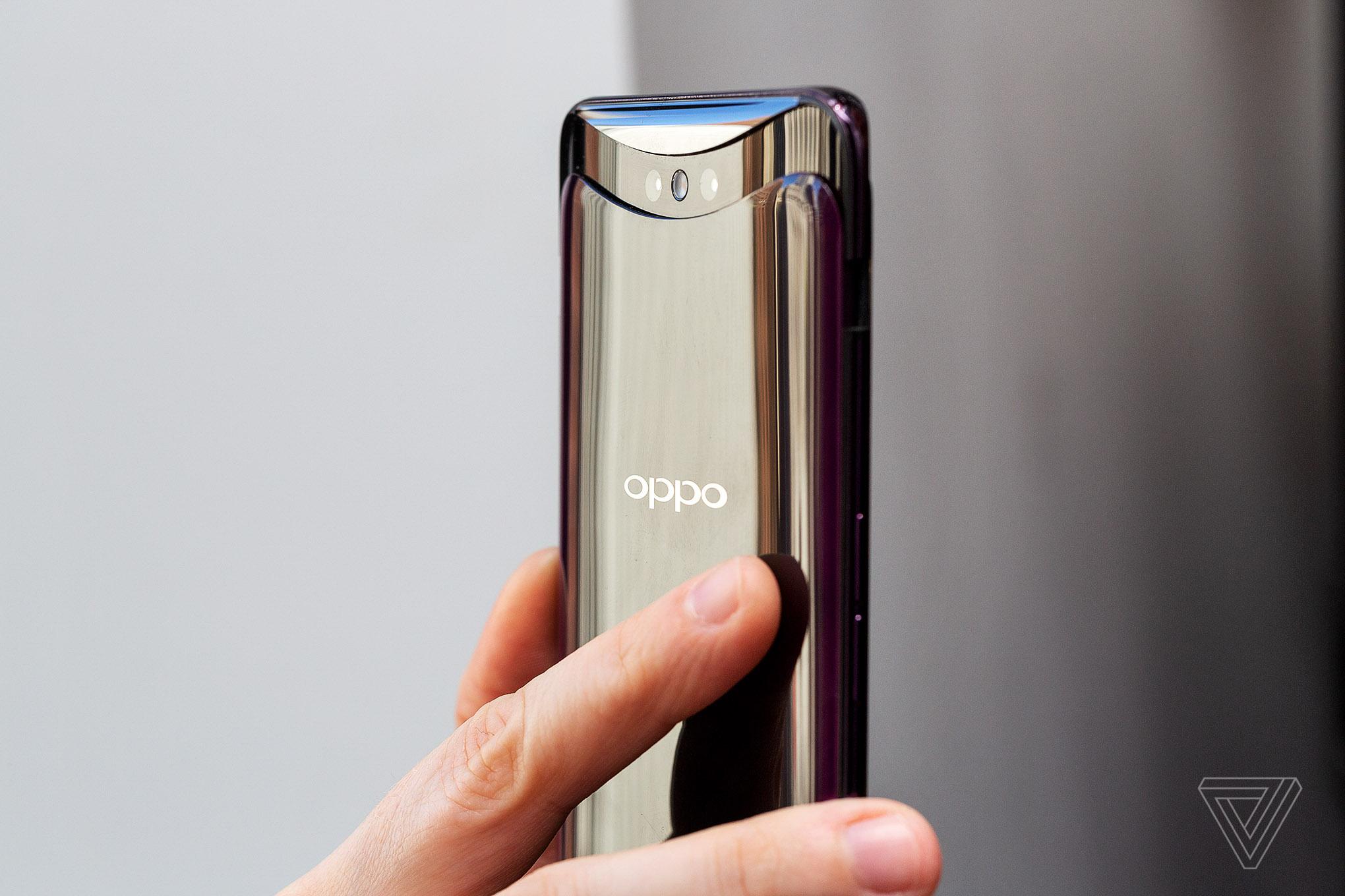 Mão segurando smartphone dourado da marca Oppo.