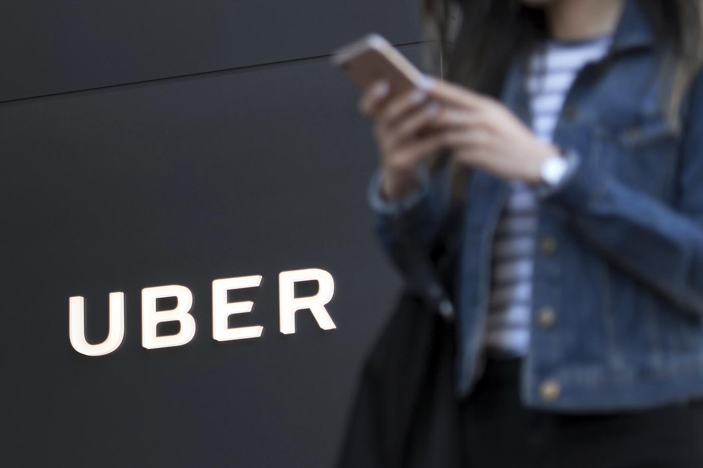 Pedestre utiliza smartphone em frente à sede da Uber em São Francisco.