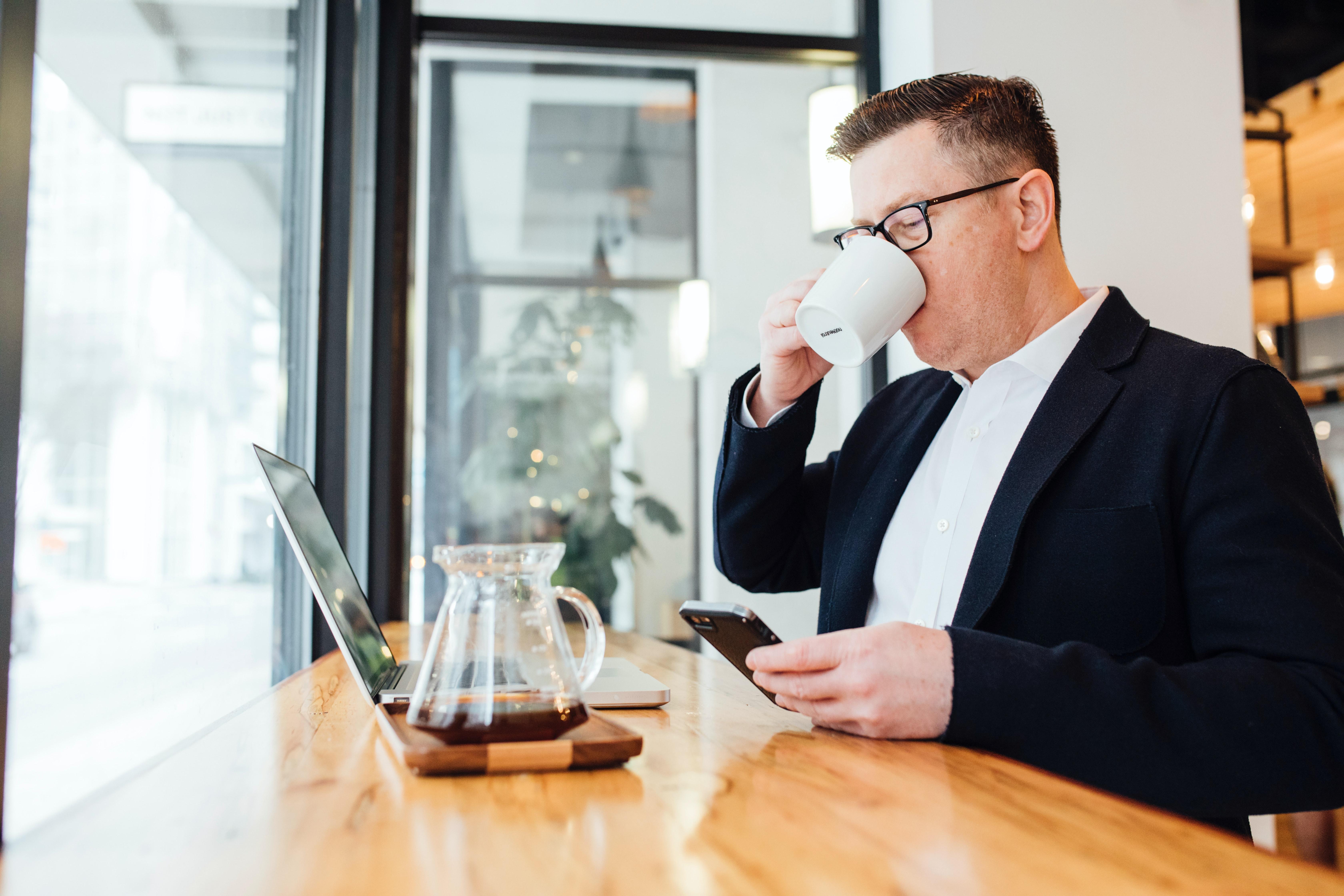 Empreendedor falando ao telefone enquanto toma café