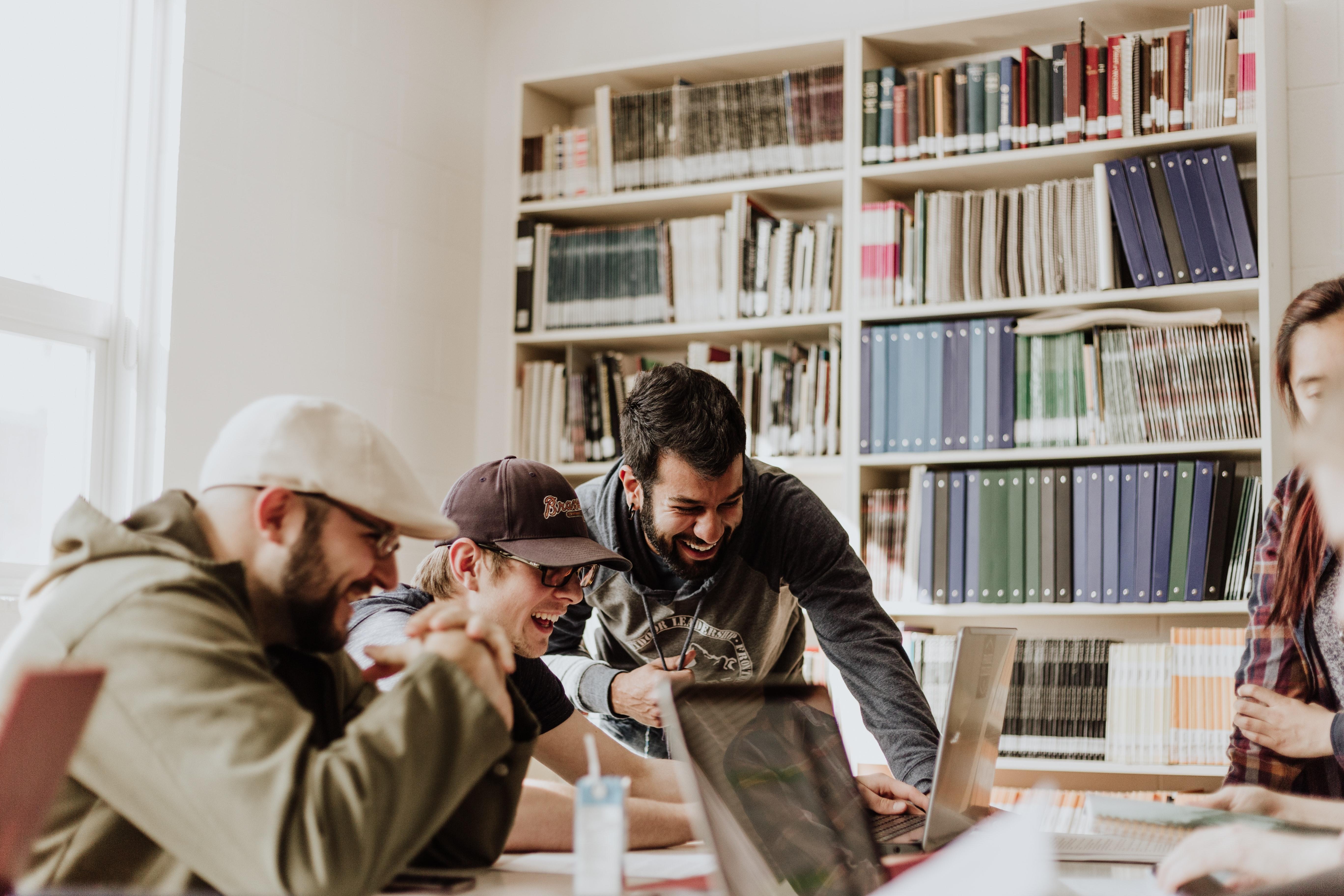 Na primeira imagem que ilustra o texto sobre Soluções para fortalecer a cultura empresarial, vemos três colegas sorrindo e rindo sobre algo que estão vendo na tela do computador.